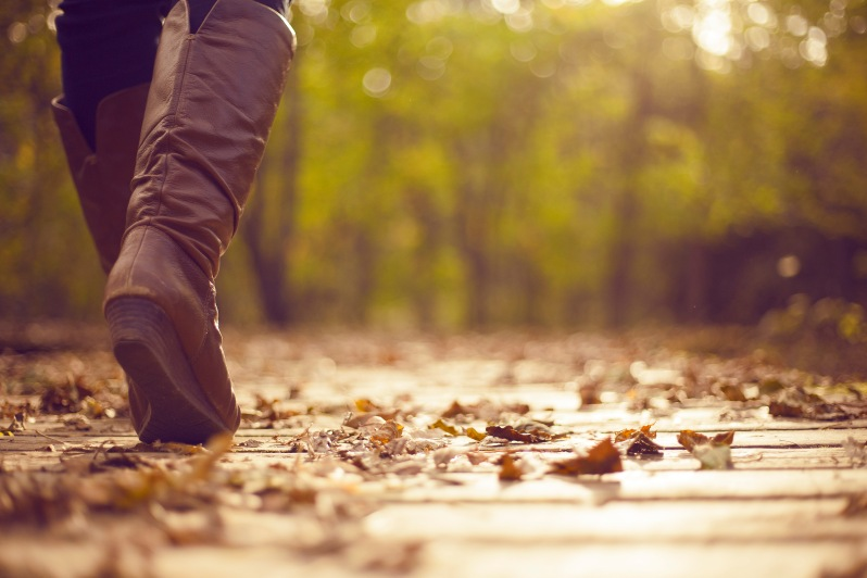A young woman walking along a boardwalk in the woods in fall wearing a jacket and riding boots